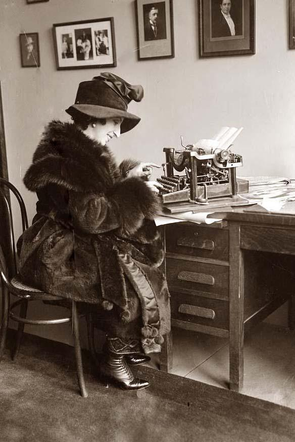 This is a photo from the 1920's showing a woman working at her desk, typing