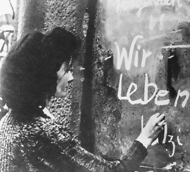"""Wir leben"" - the phrase means 'We're alive', a poignant message scrawled on the door of a bomb-striken house, to reassure friends and family"