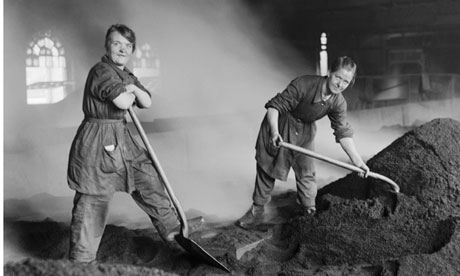 Women feed the charcoal kilns used for purifying sugar at a refinery in Scotland, circa 1916.